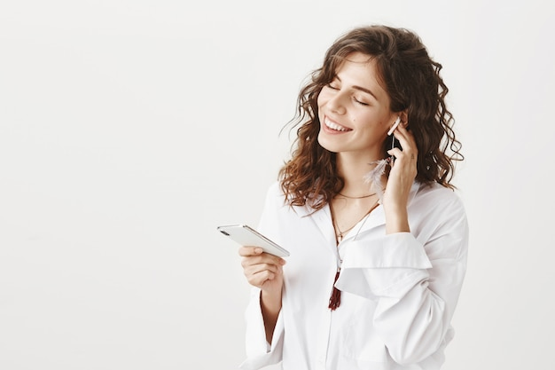 Aantrekkelijke stijlvolle vrouw luisteren muziek in draadloze koptelefoon, smartphone te houden