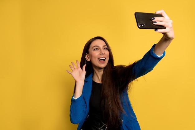 Aantrekkelijke stijlvolle vrouw met donker haar dragen blauwe jas zwaaien en selfie maken. blij meisje met lichtbruin haar selfie met zacht glimlach maken op gele muur