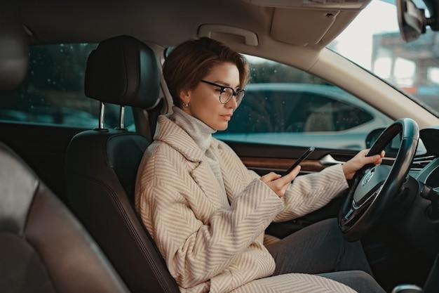 Aantrekkelijke stijlvolle vrouw zittend in de auto gekleed in jas winter stijl en bril met behulp van slimme telefoon