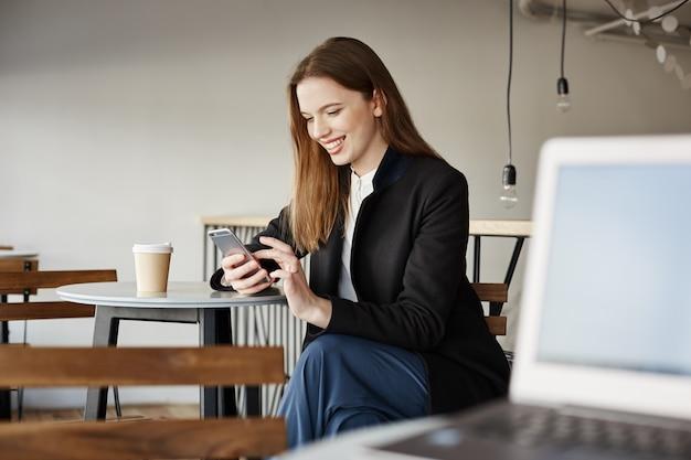 Aantrekkelijke stijlvolle vrouwelijke ondernemer te wachten in café, met behulp van mobiele telefoon