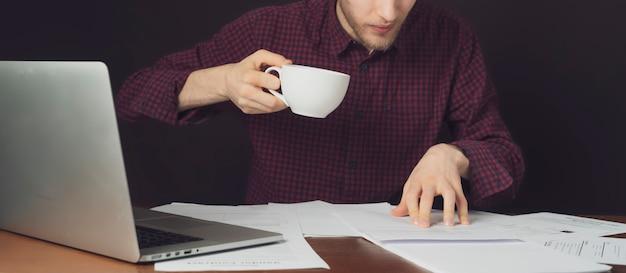Aantrekkelijke student werkt met papier en laptop en drinkt koffie op donkere achtergrond b
