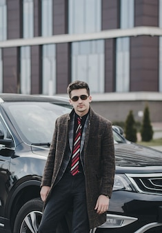 Aantrekkelijke succesvolle jonge zakenman in een pak in de buurt van zijn auto