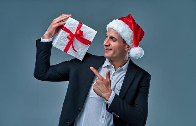 Aantrekkelijke succesvolle zakenman in een jas en shirt in een pet van de kerstman met een geschenkdoos in de studio op een grijze achtergrond.