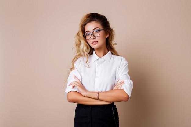 Aantrekkelijke succesvolle zakenvrouw met openhartige glimlach op zoek. leraar of werknemer. beige muur.