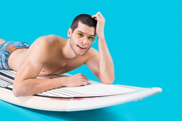 Aantrekkelijke surfer liggend op het bord