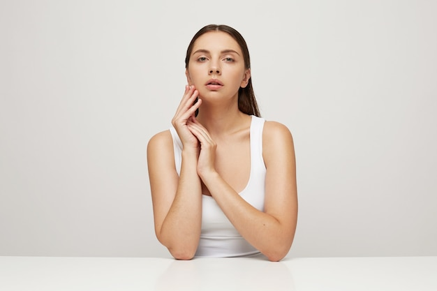 Aantrekkelijke tedere vrouw met perfect gezonde huid zit aan tafel, handen gevouwen in de buurt van het gezicht