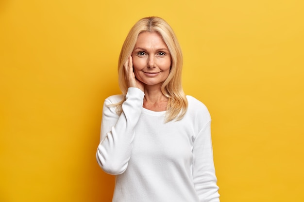 Aantrekkelijke tedere vrouw van middelbare leeftijd met blond haar heeft een gezonde en gerimpelde huid draagt minimale make-up gekleed in casual witte trui vormt binnen