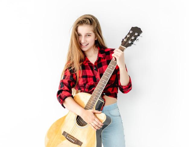 Aantrekkelijke tiener die zich met gitaar bevindt