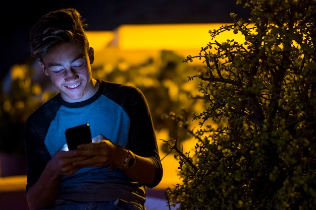 Aantrekkelijke tiener die zijn telefoon vasthoudt en gebruikt - glimlachend en lachend om zijn smartphone - jongen aan het chatten of videogames spelen