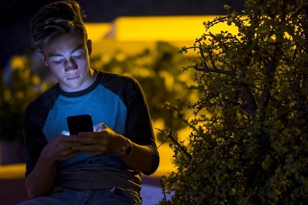 Aantrekkelijke tiener die zijn telefoon vasthoudt en gebruikt - glimlachend en lachend om zijn smartphone - jongen die 's nachts aan het chatten is of videogames speelt