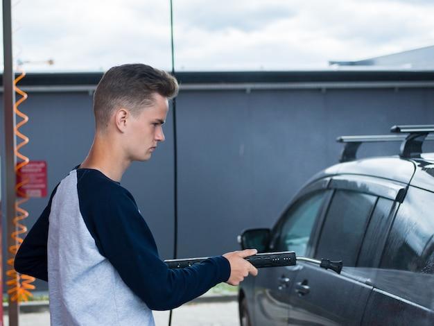 Aantrekkelijke tiener zijn auto schoonmaken bij het zelfbedieningsstation voor handmatige autowassen