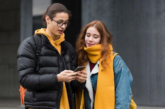 Aantrekkelijke tieners die een mobiele telefoon controleren