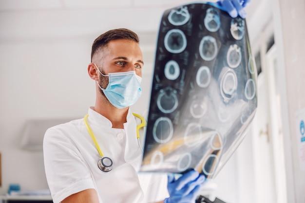 Aantrekkelijke toegewijde jonge arts die zich in het ziekenhuis met gezichtsmasker en rubberhandschoenen bevindt en röntgenfoto van de hersenen van de patiënt bekijkt.