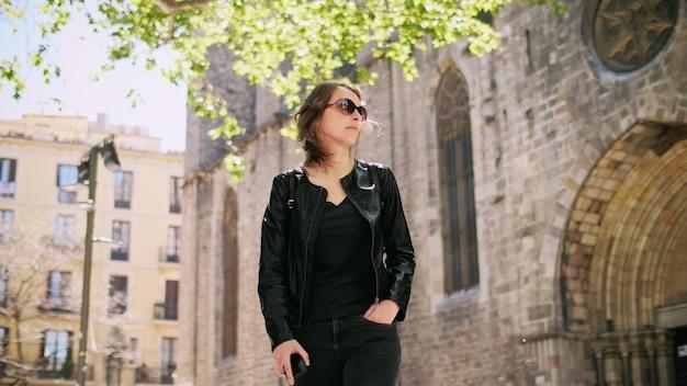 Aantrekkelijke toeristische vrouw in zonnebril met rugzak wandelen door straat. genieten van vrijheid. ze lacht en geniet van wandelen.