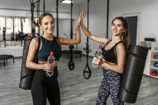 Aantrekkelijke twee jonge meisjes met een yogamat en een fles water in een moderne sportschool