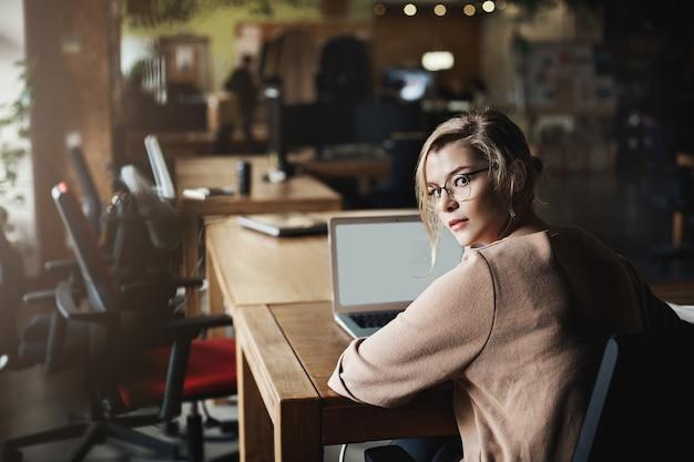 Aantrekkelijke vastberaden blanke blonde vrouw in glazen, die zich omdraait om naar de camera te kijken, wordt gebeld door een collega terwijl ze op kantoor zit, werkt via laptop en communiceert met klanten.