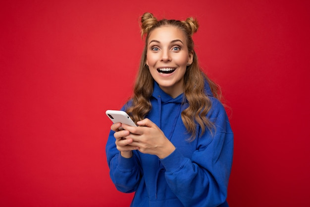 Aantrekkelijke verbaasde geschokte jonge blonde vrouw met een blauwe stijlvolle hoodie die geïsoleerd staat over een rode achtergrond sms-bericht via de telefoon kijkend naar de camera