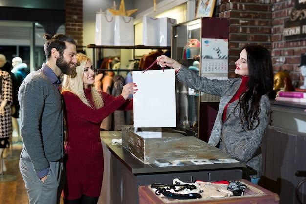 Aantrekkelijke verkoopster die een tas met kleren overhandigt aan een mooi stel mannen en vrouwen