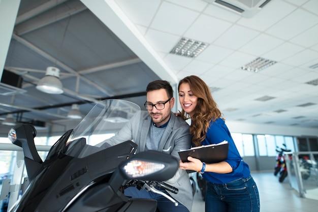 Aantrekkelijke verkoopvrouw die klant helpt welke motorfiets te kopen