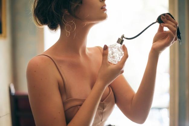 Aantrekkelijke verleidelijke sensuele stijlvolle vrouw in boho jurk zitten vintage retro café parfum houden