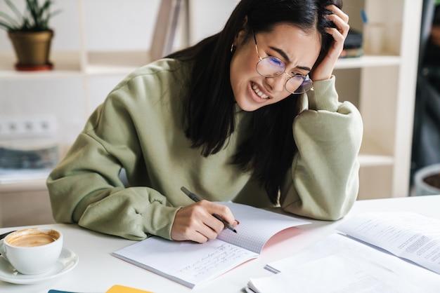 Aantrekkelijke vermoeide, overstuur jonge studente die studeert aan de universiteitsbibliotheek, aan het bureau zit, zich klaarmaakt voor examens
