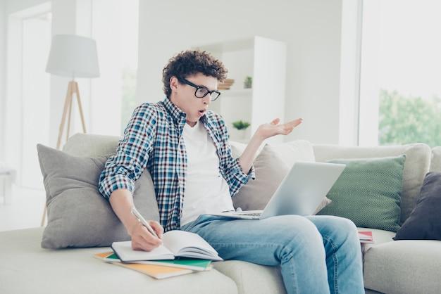 Aantrekkelijke verwarde man student nerd thuis universiteit huiswerk