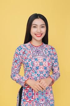 Aantrekkelijke vietnamese vrouw die traditioneel kostuum draagt, dat op gele achtergrond wordt geïsoleerd