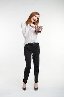Aantrekkelijke visagist of koreaanse visagist die make-upborstels en een palet van oogschaduw op wit houdt