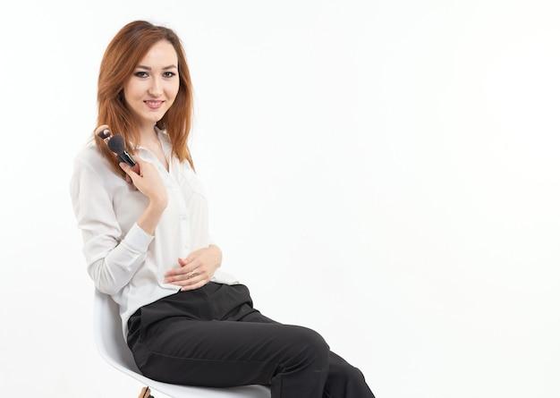 Aantrekkelijke visagist of koreaanse visagist die make-upborstels op witte achtergrond houdt