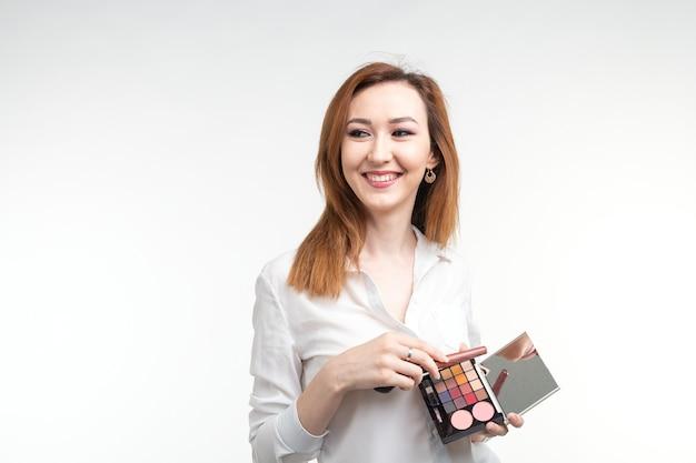 Aantrekkelijke visagist of koreaanse visagist met make-upborstels en een palet van oogschaduw op witte achtergrond