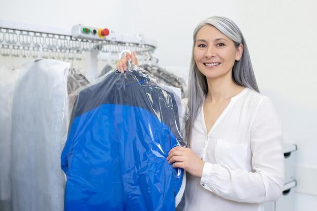 Aantrekkelijke volwassen glimlachende vrouw die schoongemaakte kleren in dekking houdt die zich dichtbij stomerij teller bevinden