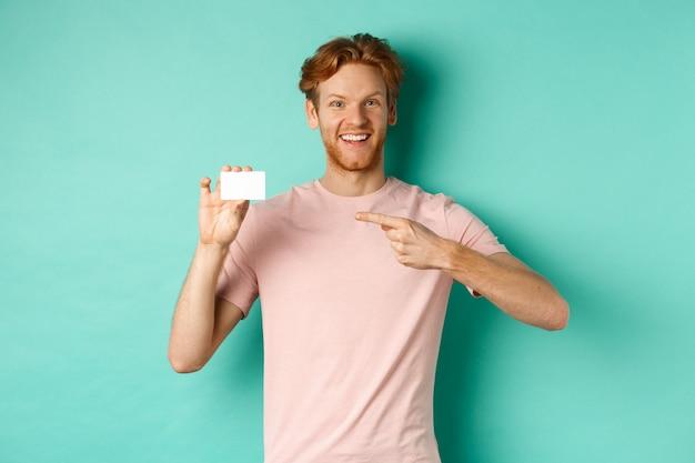 Aantrekkelijke volwassen man met baard en rood haar wijzende vinger naar plastic creditcard, tevreden glimlachend in de camera, staande over turkooizen achtergrond