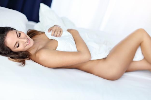 Aantrekkelijke volwassen naakte vrouw die 's ochtends in bed ligt
