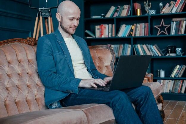 Aantrekkelijke volwassen succesvolle lachende kale man met baard in pak werken op laptop