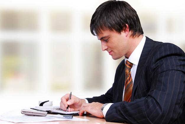 Aantrekkelijke volwassen volwassen man zit van de tafel en werkt