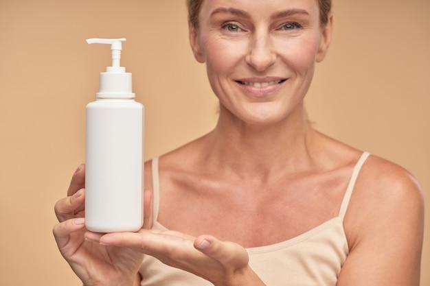 Aantrekkelijke volwassen vrouw die een pot crème vasthoudt