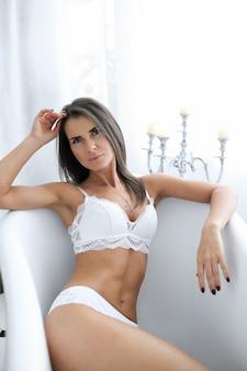 Aantrekkelijke volwassen vrouw in erotische witte lingerie in de badkuip