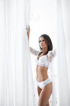 Aantrekkelijke volwassen vrouw in erotische witte lingerie