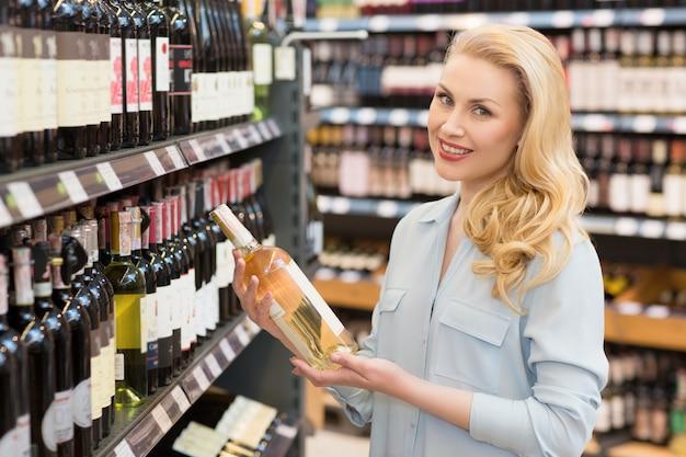 Aantrekkelijke volwassen vrouw kopen van wijn bij de supermarkt