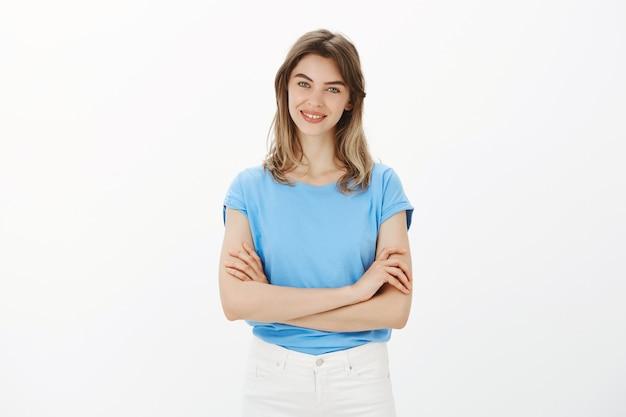 Aantrekkelijke volwassen vrouw kruis armen borst en glimlachend zelfverzekerd
