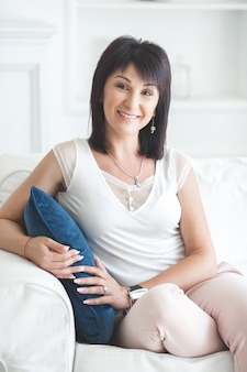 Aantrekkelijke volwassen vrouw zittend op de bank binnenshuis. mooie vrouw van middelbare leeftijd thuis. portret van 35-40 jaar vrouwen.