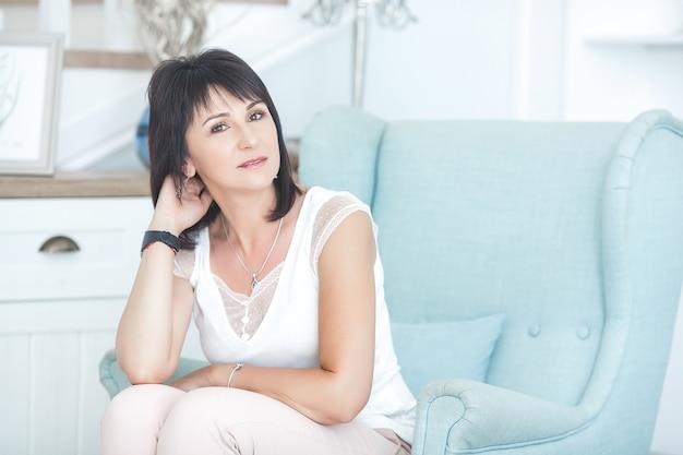 Aantrekkelijke volwassen vrouw zittend op de bank binnenshuis. mooie vrouw van middelbare leeftijd thuis.