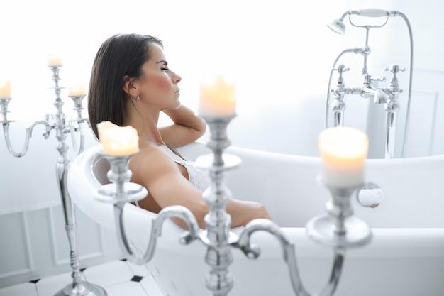 Aantrekkelijke volwassen vrouwenvrouw die een ontspannend bad nemen