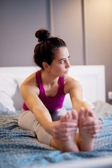 Aantrekkelijke vorm sportieve vrouw van middelbare leeftijd zittende yoga houdingen op het bed voor het slapen.