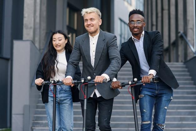 Aantrekkelijke vreugdevolle multiraciale kantoorcollega's rijden op elektrische scooters in de buurt van een prachtig architectonisch gebouw.