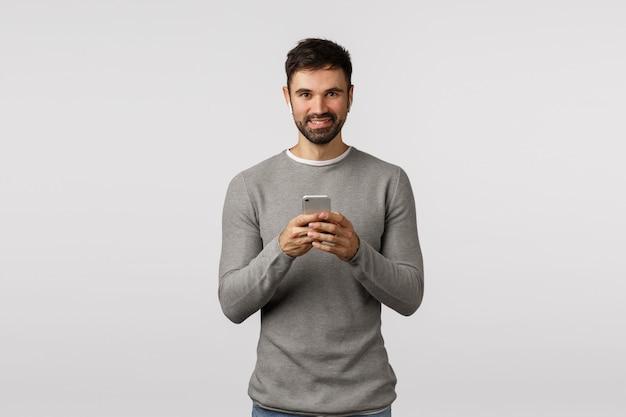 Aantrekkelijke vriendelijk ogende blanke man in grijze trui, met smartphone, draadloze koptelefoon dragen, oortelefoons gebruiken om muziek te luisteren, video bekijken in openbare ruimte