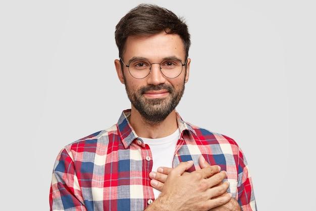Aantrekkelijke vriendelijke goedaardige man houdt beide handpalmen op het hart, spreekt zijn liefde uit voor mensen, heeft een tevreden gelaatsuitdrukking