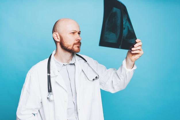 Aantrekkelijke vriendelijke kale bebaarde arts kijken naar de röntgenfoto geïsoleerd op blauwe achtergrond