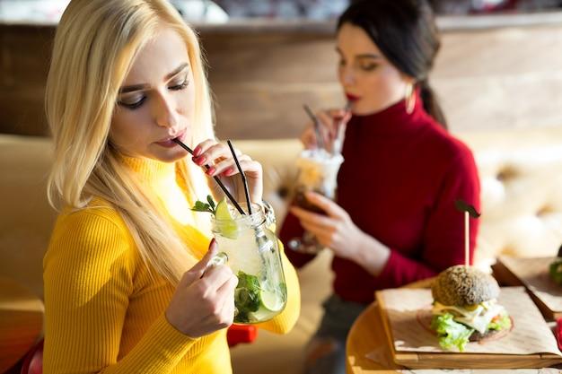 Aantrekkelijke vrienden cocktails drinken samen. twee mooie jonge vrouw zitten aan de bar met drankjes