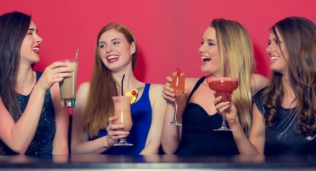Aantrekkelijke vrienden die cocktails vasthouden